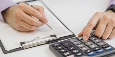 Close-up Of Businessman Calculating Invoices Using Calculator
